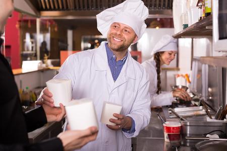 fast food: Hombre alegre compra de comida r�pida en caja de cart�n en el caf�