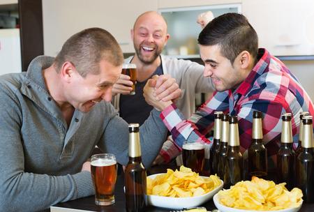 borracho: Hombres felices y borrachos armwrestling, su amigo de apoyo en la habitaci�n