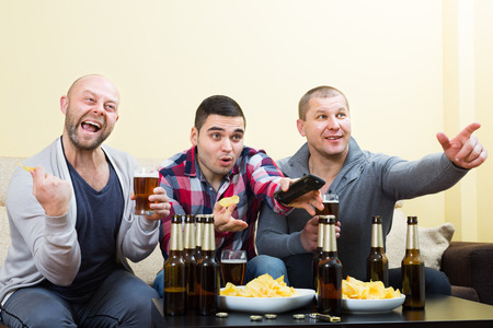 fandom: Three excited male friends watching football game with beer at home