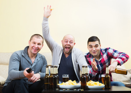 fandom: Three male sport happy fans watching hockey game heatedly in livingroom