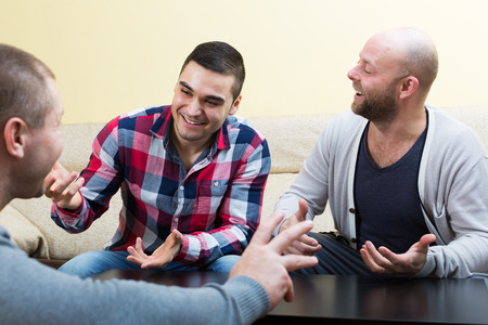 party friends: Three adult men talking  at living room Stock Photo