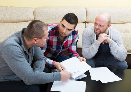financial issues: Three men with documents discussing financial issues