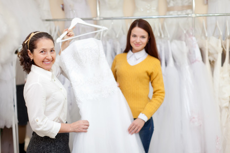 bridal gown: Woman helps the bride in choosing bridal gown at shop of wedding fashion. Focus on mature Stock Photo