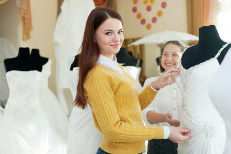Two women chooses bridal outfit at wedding boutique. Focus on young photo