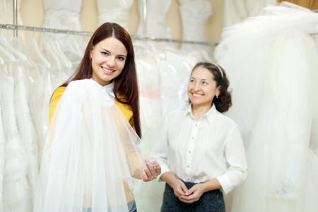 Girl chooses bridal veil at shop of wedding fashion. Friendly shop consultant helps her photo
