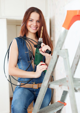 studio happy overall: Sexy girl with drill on stepladder in interior