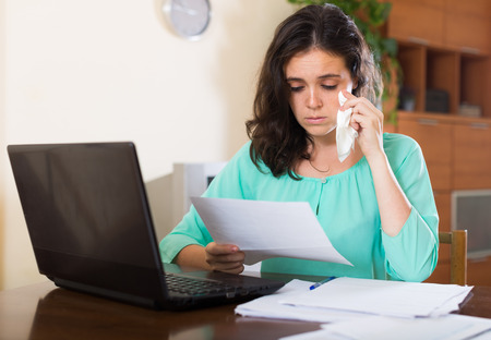 parsimony: Sad woman with financial documents and laptop at table in home interior Stock Photo