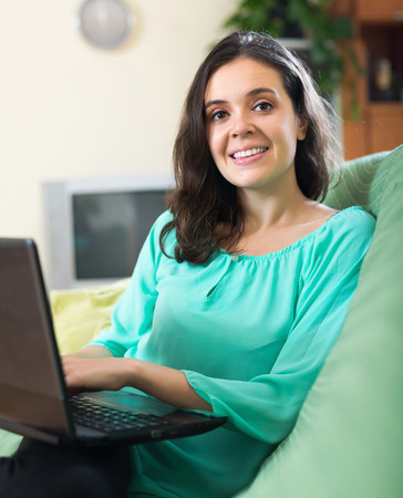 netbook: Young positive girl looking at netbook in living room