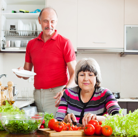 doing chores: senior man in red and  woman  doing chores together Stock Photo