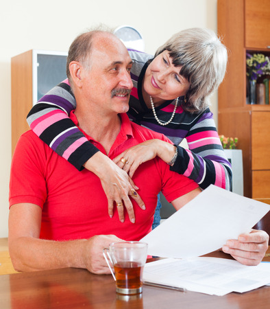 utility payments: Loving mature  couple with financial documents at table in home interior Stock Photo