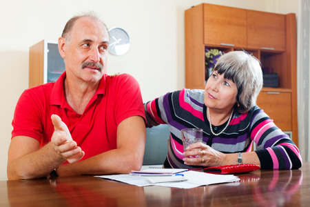 financial problems: Financial problems in the family. Mature woman asks for money from her husband for the purchase