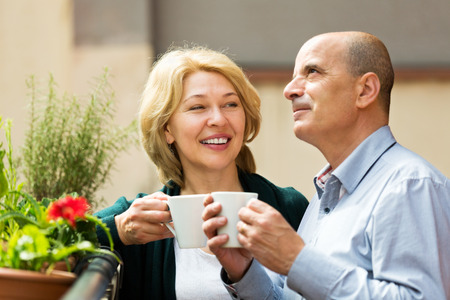 Positive  mature couple having morning coffee at balcony and smiling photo