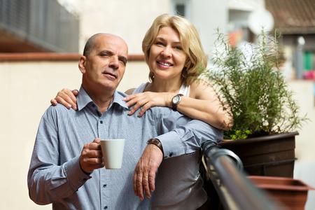 Smiling elderly  couple having morning coffee at balcony photo