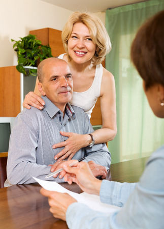 private insurance: Friendly elderly  couple discussing details of private insurance with agent