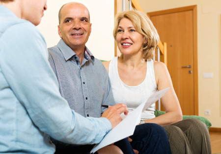 private insurance: Mature  couple discussing details of private insurance with friendly agent Stock Photo