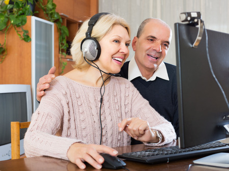 global retirement: Loving mature couple talking with someone online and smiling