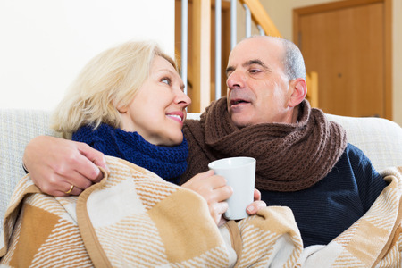spouses: Elderly smiling spouses under blanket drinking tea on couch