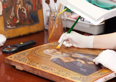 Art restorer works on old gilded icon with brush at  workshop photo