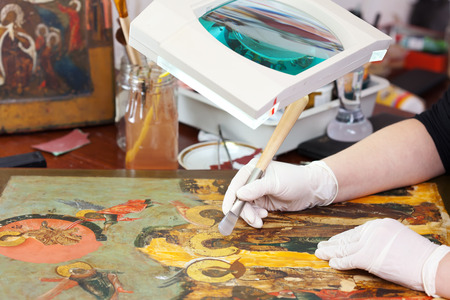 restoration: restoration of Christian icon with agate burnisher at workshop