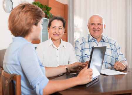 outreach: Mature couple answer questions of outreach worker with laptop in home Stock Photo