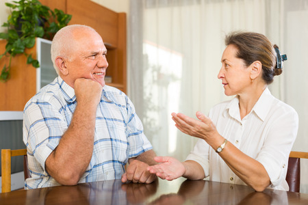 2 50: Indoor portrait of elderly couple talking together in home interior. Focus on man