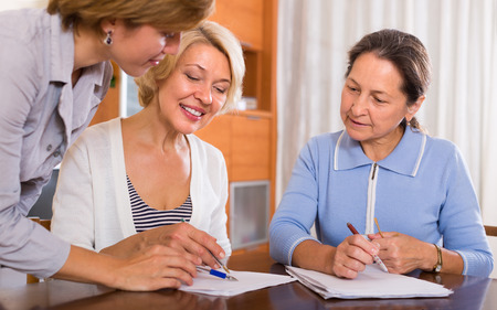Two smiling positive female pensioners signing documents with public notary photo