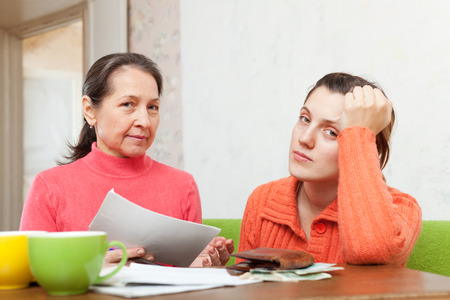 mother scolds adult daughter for utility payments bills or credits. Focus on mature photo
