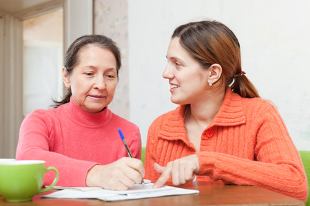 Two positive women fills in the questionnaire at  home photo