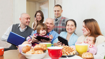 Happy multigeneration family using electronic devices over tea  in home photo