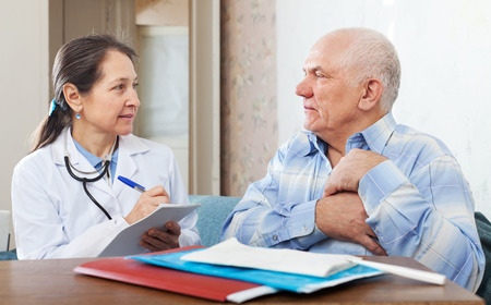 Mature man complaining  to doctor about heartache at medical hospital photo
