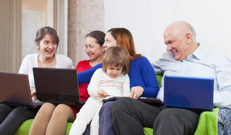 Happy family sits  in livingroom with few laptops at home photo