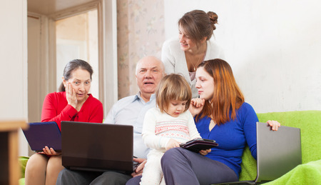 Happy family of with various portable computers on sofa at home photo