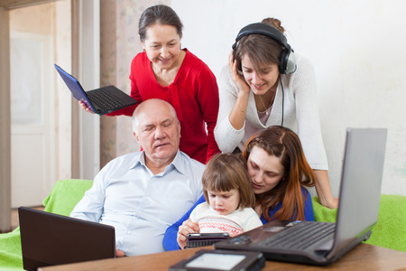 family uses few various electronic devices in home interior photo