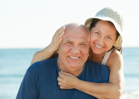 older women: Portrait of smiling mature couple against sea and sky Stock Photo