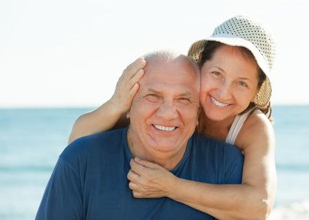 mujeres mayores: Retrato de la sonriente pareja madura contra el mar y el cielo