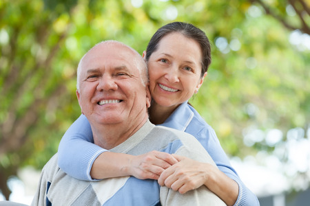 50s man: Portrait of cheerful mature couple together in autumn park Stock Photo