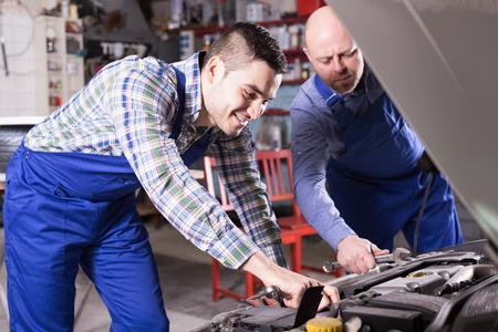 journeyman: Portret to professional mechanics repairing car of client Stock Photo