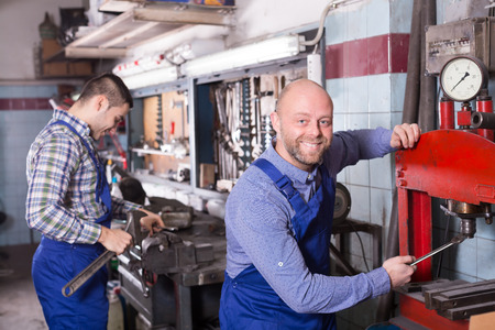 toiling: Two workmen toiling in locksmiths workshop and smiling