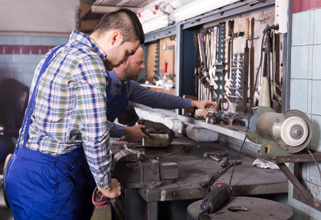 metalworker: Two adult men are working in a workshop with various tools Stock Photo