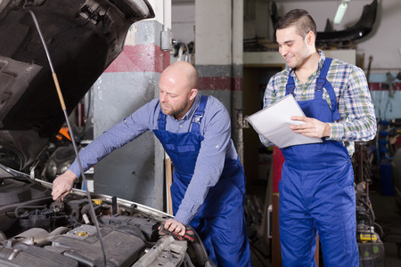 work workman: Workman calculating the price of work at the auto repair shop Stock Photo