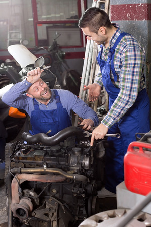 mounting: Smiling mounting specialists working at auto repair shop. Stock Photo