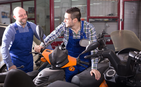 motorized: Specialists in coveralls working with motorized bicycles at repair shop Stock Photo