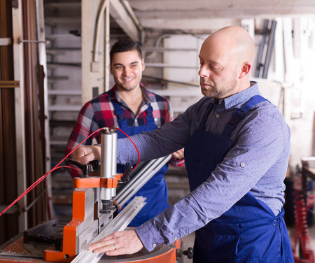 enginery: Two positive workmen in uniform working on a machine in PVC shop