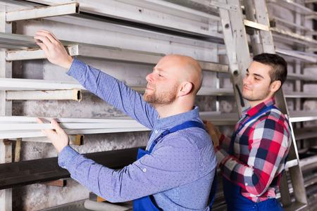 enginery: Positive workmen choosing PVC window profile at factory Stock Photo