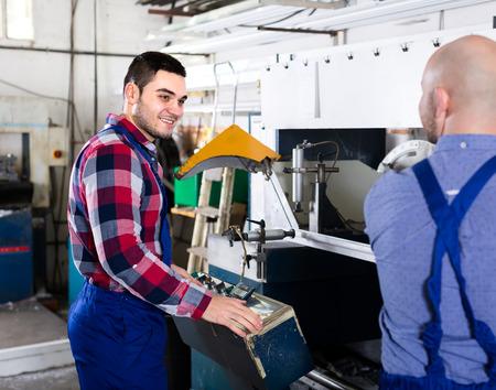 skilled operator: Workmen using a lathe to cut aluminum window frames Stock Photo