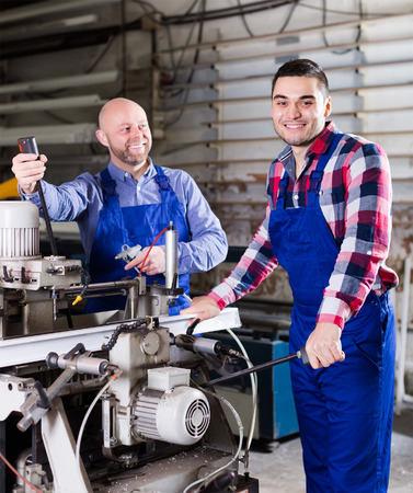 skilled operator: Two cheerful men in uniform working on a machine in PVC shop and smiling