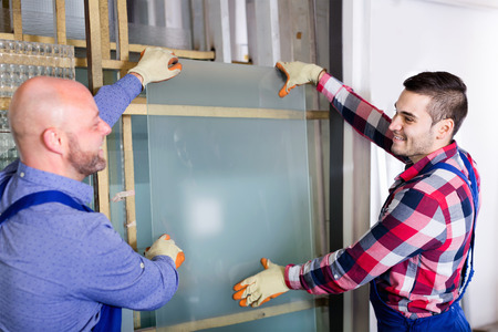 glasswear: Two careful workers  working  with glass at modern factory Stock Photo