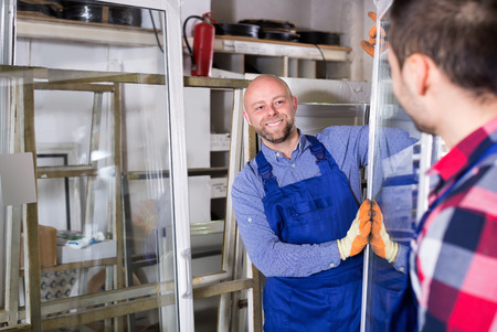 enginery: Two  workers inspecting windows at workshop Stock Photo