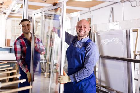 Twee productiemedewerkers inspecteren ramen op workshop Stockfoto
