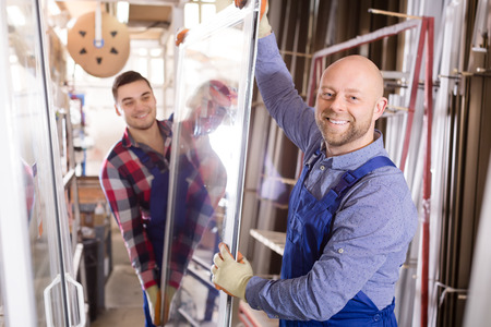 toolroom: Portrait of two workers in coverall working with PVC window at factory